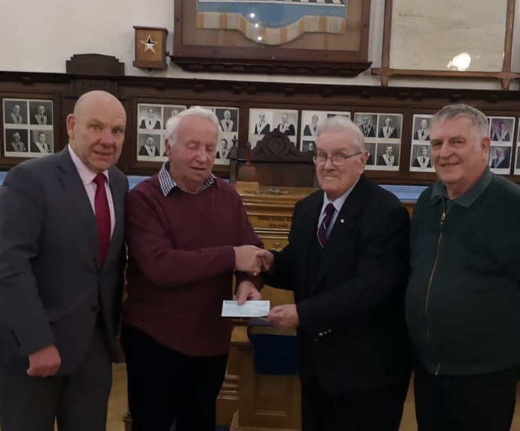 The photo shows W. B Geoff Haigh (oldest member of Colne Valley Lodge) presenting the cheque to Paul Webley (secretary of the friends of the The Peter Brook Centre), the other people to the outside are Andrew Coulson (Charity Steward of Colne Valley Lodge) and Alan Marchington (Treasurer of the Friends of The Peter Brook Centre).